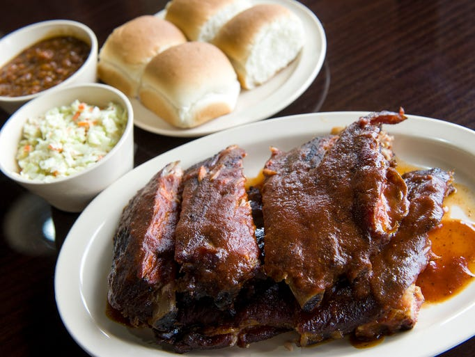 A full slab of ribs with rolls, slaw and beans at Neely's