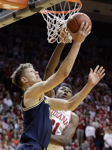 Michigan's Moritz Wagner, left, shoots against Indiana's