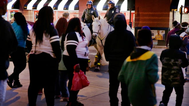 IMPD mounted patrol officers Ed Zehner (left, with horse Colonel) and Jimmy Parent (with horse Stretch) watched as a large group of teens exited Circle Centre mall on April 2, 2016.