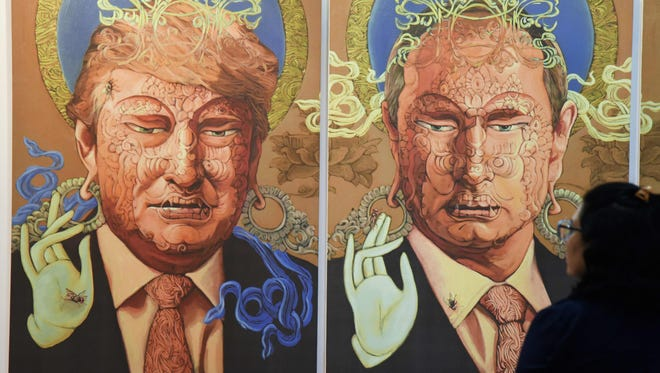 A visitor looks at a painting representing President Trump and Russian President Vladimir Putin made by Nepalese artist Sunil Sidgel at the India Art Fair in New Delhi on Jan. 2, 2017.