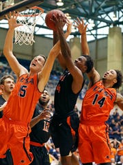 UTEP's Lee Moore, center, grabs for a rebound between UTSA's Lucas O'Brien, left, and Ryan Bowie during second half action Saturday at the Convocation Center in San Antonio.