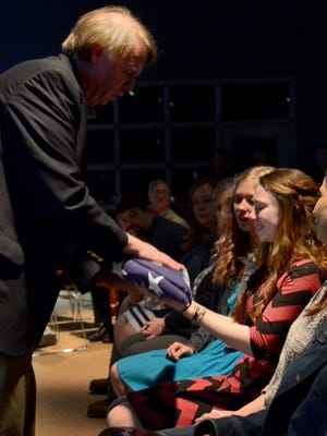 Madison County Sheriff John Mehr presents an American flag to Taylor Doty during the memorial service for her father, Deputy Matthew Doty, Thursday evening at Englewood Baptist Church.