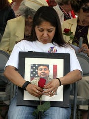 "Karina Loeza-Gasca holds a portrait of her brother, SSG Roberto Loeza Jr. during the Memorial Day ceremony at Fort Bliss National Cemetery on Monday. Loeza, a Mountain View High School graduate, was killed in Afghanistan on May 25, 2012. ""He's missed every day,"" she said."