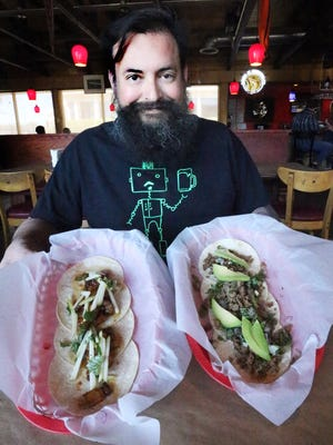 Rulis Gonzalez shows two of his signature tacos. The sirloin toreado at left, and the pork belly in teriyaki sauce tacos at right.