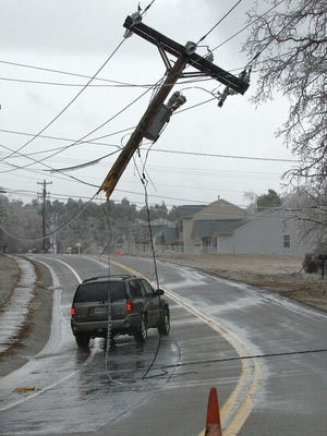 A broken power pole hangs from utility lines following a massive ice storm in 2005.