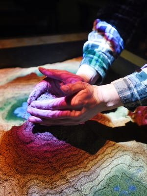 In this Thursday, May 17, 2018 photo, sophomore Cody Bicknell builds a landscape in the augmented reality sandbox before the start of Jaret Stump's class at Glacier High School in Kalispell, Mont. Stump said, many of the students love to play with the sandbox, even stopping in between their classes. ((Brenda Ahearn/The Daily Inter Lake via AP)