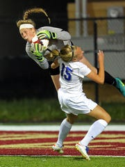 McAuley goal keeper Camryn Glasmeier goes airborne to make a save on the shot by Mercy's Emma Wessel in the girls soccer match between the McAuley Mohawks and the Mercy Bobcats at Western Hills High School.