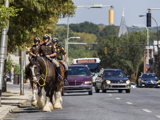 Members of the New Castle County mounted police force patrol around Rodney Square on Friday morning.