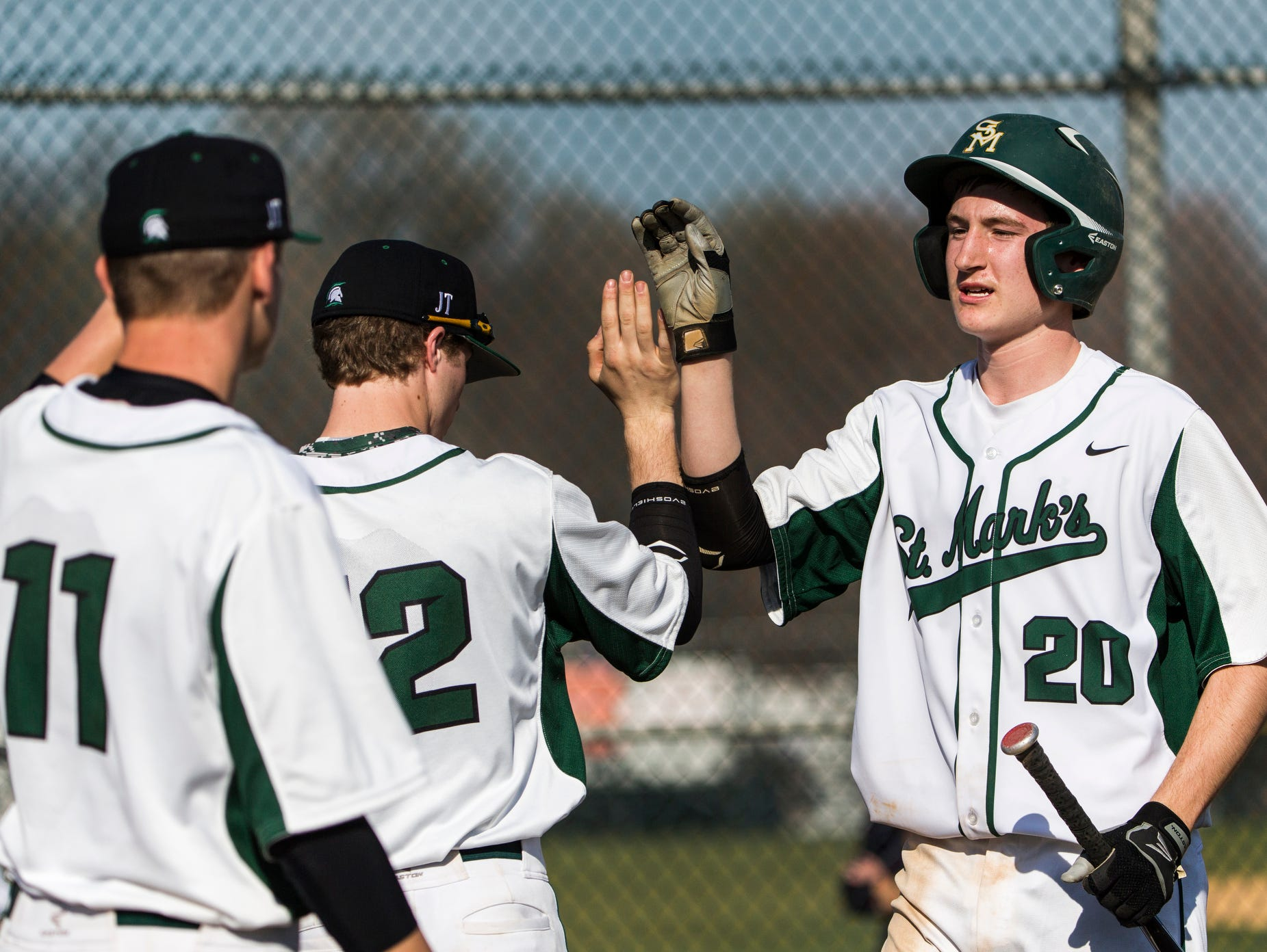 St. Mark's Christopher Ludman (No. 20) celebrates with teammates after scoring a run in St. Mark's 12-0 win over Hodgson at St. Mark's High School on Wednesday afternoon.