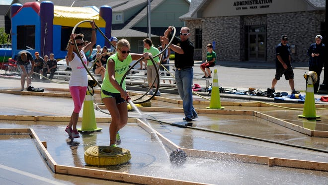 A team rushes to the finish line at the water bowling contest on Railroad Avenue on Saturday, Aug. 6, in Albany.