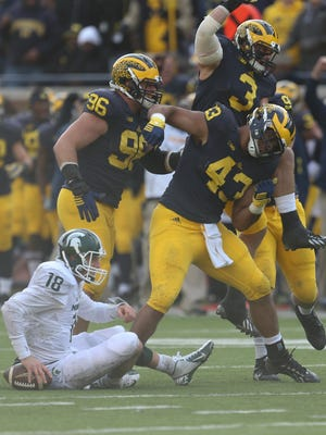 Michigan's Chris Woemley  (43) celebrates his sack of Michigan State QB Connor Cook during the second quarter Saturday.