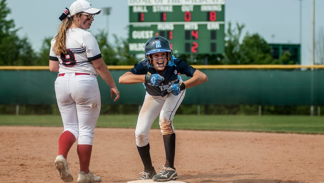 Richmond's Carley Barjaktarovich looks to the dugout and celebrates after getting safely to first on Divine Child's Kerstin Hamann during a quarterfinal softball game Tuesday, June 13, 2017 at Novi High School.