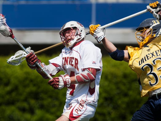 Denver's Wesley Berg, left, dugs under the stick of Drexel's Tyler Houchins (No. 33) in the first quarter of an NCAA Tournament quarterfinal game between Denver and Drexel at Delaware Stadium in Newark on Sunday afternoon, May 18, 2014. Denver defeated Drexel 15-6.