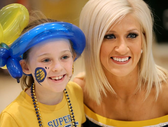 Pacemate Laure Beth has her photo taken with Pacers fan Jade Shafer, 8 of St. Louis, before the start of the Saturday's Eastern Conference playoff game against the Atlanta Hawks at Bankers Life Fieldhouse on April 19, 2014.