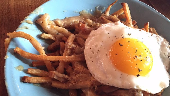 Poutine, topped with a fried egg, at Tela Bar and Kitchen