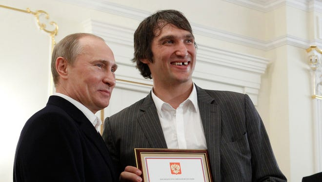"""FILE - In this May 29, 2012, file photo, Russian national ice hockey team member Alexander Ovechkin, right, holds a certficate of recognition given to him by President Vladimir Putin, left, in the Novo-Ogaryovo residence outside Moscow. Washington Capitals captain Alex Ovechkin has voiced his support for Vladimir Putin ahead of the upcoming Russian presidential elections. Ovechkin posted a message in Russian on his Instagram account Thursday, Nov. 2, 2017,  announcing he's starting """"a social movement called Putin Team."""" From right in the background are Russian ice hockey federation president Vladislav Tretyak and Russia's captain Ilya Nikulin. (AP Photo/Sergei Karpukhin, Pool, File)"""