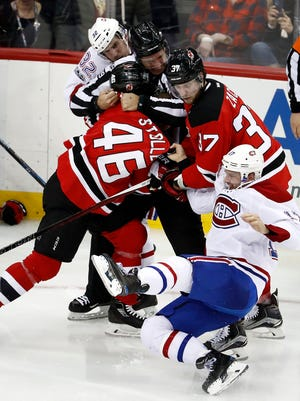 Linesman Steve Miller, center, struggles to separate Montreal Canadiens center Torrey Mitchell (17) and center Brian Flynn (32) from Devils center Pavel Zacha (37) and defenseman Karl Stollery (46) during the third period of a game, Friday, Jan. 20, 2017, in Newark. The Canadiens won 3-1.