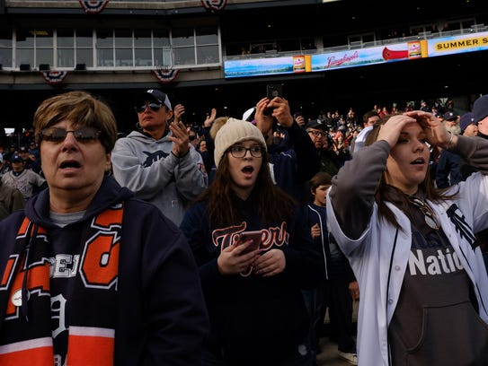 Fans react to a challenge call during the 9th inning