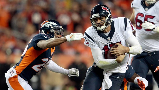 Houston Texans quarterback Brock Osweiler (17) runs for a first down as Denver Broncos cornerback Chris Harris (25) defends during the second half of their game on Monday in Denver. The Broncos won 27-9.