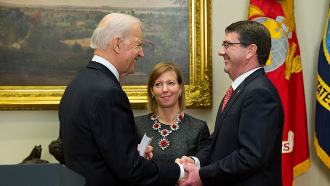 Stephanie Carter watches at center as her husband Ash Carter, right, shakes hands with Vice President Joe Biden after being sworn in as the new Defense Secretary, Tuesday, Feb. 17, 2015, in the Roosevelt Room of the White House in Washington.  Carter, 60, is President Barack Obama's fourth secretary of defense. (AP Photo/Evan Vucci)