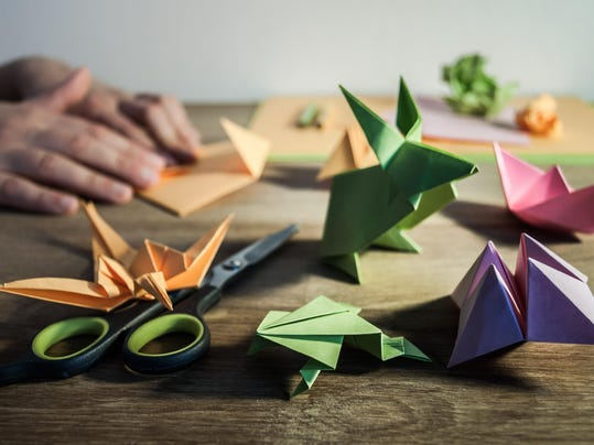 Origami figures on the table with hands in the backdground.