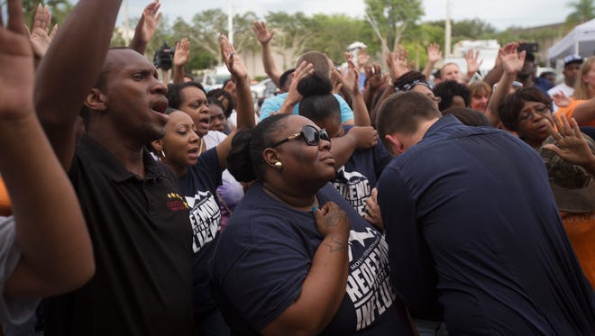 Shaniqua Young,center, takes part in prayer service in front of Club Blu on Monday evening.  It was the scene of a mass shooting where two teens died and at least 16 injured.