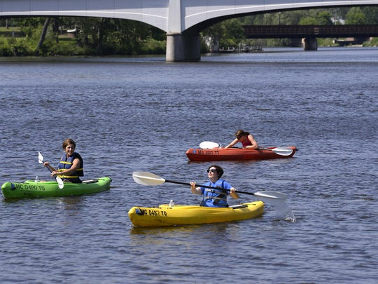 Kayakers paddle on the Grand River downtown, starting outside the Lansing City Market at River Town Adventures. The kayak rentals are just another draw to downtown and the Lansing River Trail.
