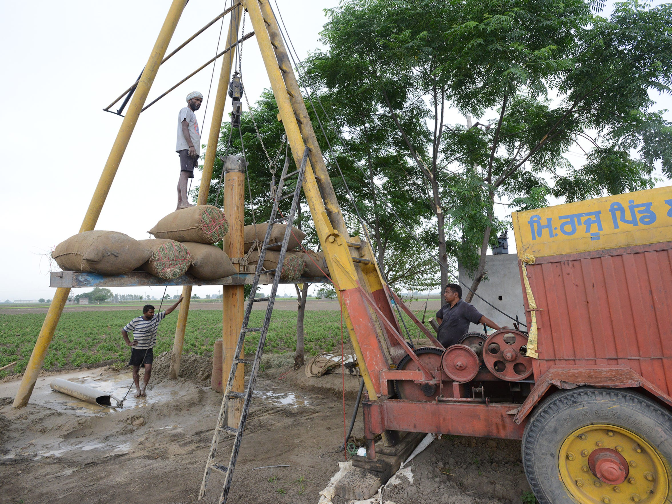 Workers install a tube well in the sandy alluvial soil of Punjab, India. Sections of steel pipe are pounded into the ground as soil is gradually removed from the hole.