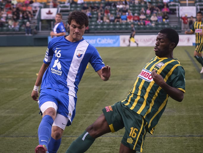 Brock Granger, left, and Levi Houapeu meet at the ball in the first half of a game between the Rochester Rhinos and Dayton Dutch Lions on June 20, 2014.