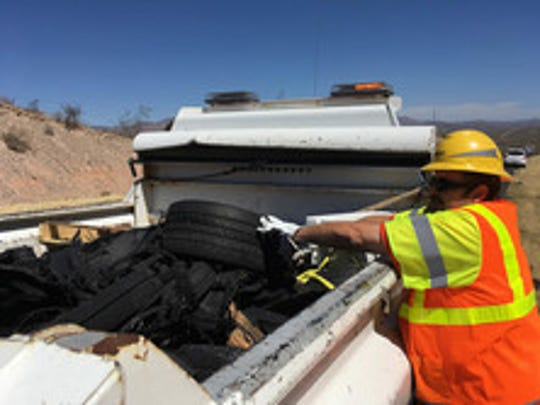 An ADOT crew removes tire debris from the shoulder of I-17 near Black Canyon City