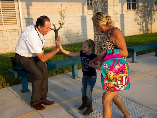 Everglades City School Principal Jim Ragusa, greets Lylah Pasiuk, 4, a pre-K student, as well as her great-aunt Helen Daniels, as the two make their way into school Monday, Sept. 25, 2017, in Everglades City, Fla. Fifteen days after Hurricane Irma made landfall, students from southeastern Collier county came closer to a sense of normalcy as they returned to Everglades City School for their first day back since the storm.
