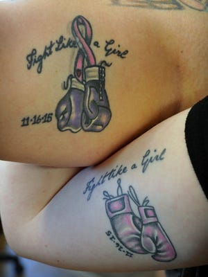 Brittany Young and Shelby Young show off tattoos they got to mark the date their mother Darla Sanders began her battle with cancer, November 2015. Darla has a similar tattoo on her ankle, and her husband, Michael Sanders, has one on the top of his shaved head. Darla and Michael own and operate Designmasters Tattoo Studio. Tattoo and body modification artists may soon have a chance to participate in tempoary events within the city if council passes an ordinance change during their meeting Tuesday,  Dec. 5.