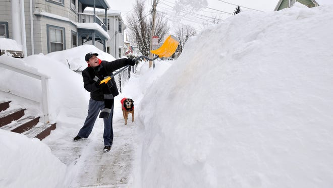 Lee Anderson adds to the pile of snow beside the sidewalk in front of his house in Somerville, Mass., on Feb. 10, 2015.