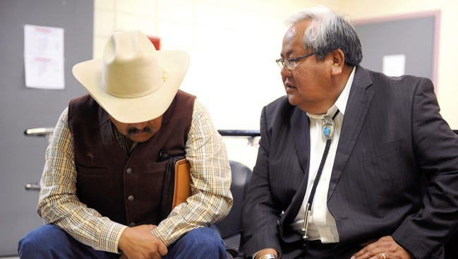 Former Navajo Nation Council Speaker Lawrence T. Morgan, left, and Johnny Naize, the council's current speaker, wait on March 11, 2014, outside the judicial district office for their arraignment hearings at Window Rock District Court in Window Rock, Ariz.