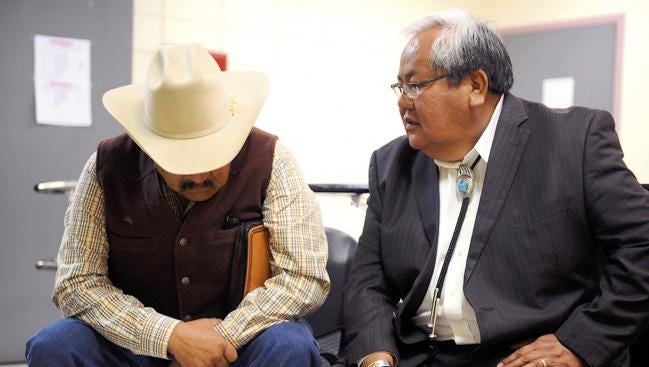 Former Navajo Nation Council Speakers Lawrence T. Morgan, left, and Johnny Naize wait on March 11, 2014, outside the judicial district office for their arraignment hearings in Window Rock, Ariz.