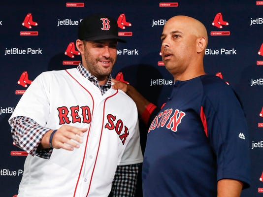 Boston Red Sox baseball player J.D. Martinez, left, meets with manager Alex Cora during a news conference announcing his signing with the team, Monday, Feb. 26, 2018, in Fort Myers, Fla. (AP Photo/John Minchillo)