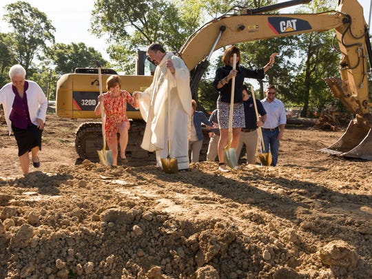 Rev. Brian Taylor helps elementary principal Becky Trouille up a dirt mound during a mass and ceremony celebrating St. Genevieve Catholic School middle campus' groundbreaking for a new cafetorium in Lafayette April 7, 2016.