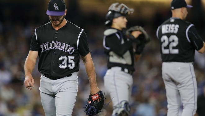 Colorado Rockies starting pitcher Chad Bettis, left, leaves the mound after he was pulled by manager Walt Weiss during the fifth inning of a baseball game against the Los Angeles Dodgers, Saturday, Sept. 24, 2016, in Los Angeles.