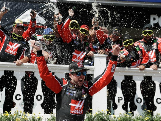 Kurt Busch celebrates with his team in victory lane after winning the NASCAR Sprint Cup series auto race at Pocono Raceway, Monday, June 6, 2016, in Long Pond, Pa.