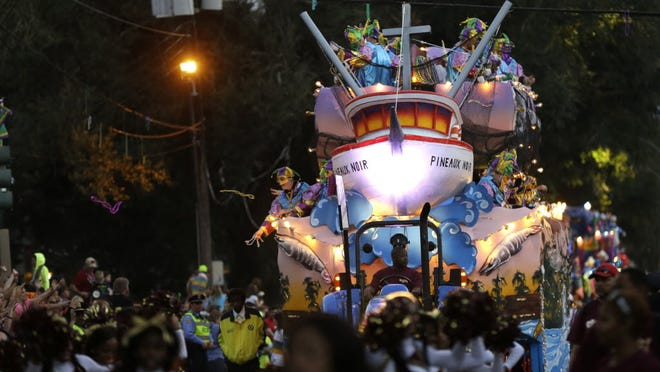 Members of the Krewe of Bacchus Mardi Gras parade throw beads from floats as the super-krewe rolls down Napoleon Ave. in New Orleans on March 2.