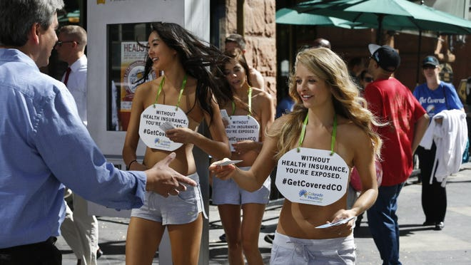 Models hand out fliers in Denver last year encouraging people to buy insurance on Colorado's health care exchange.