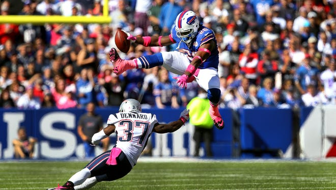 Buffalo running back Anthony Dixon leaps over New England's Alfonzo Dennard  during this play on Sunday. The Patriots earned their 21st victory in the last 22 meetings with the Bills.