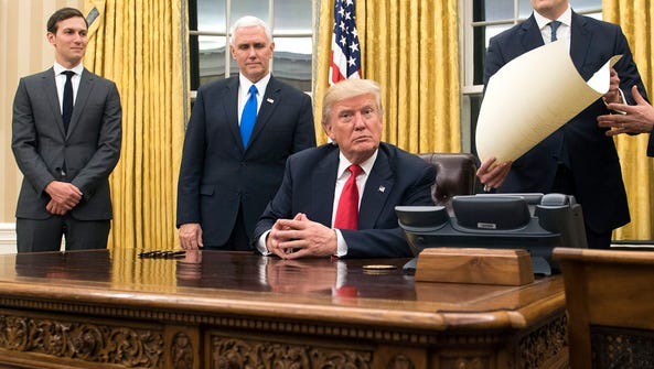 President Donald Trump sits in the Oval Office after
