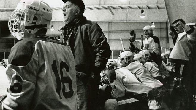 Dave Roy gives instructions to his players while serving as coach of the club hockey team.