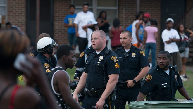 Members of the Montgomery Police Department attempt to calm the situation amid a large crowd of people. Police responded to a shooting at the 3800 block of Smiley Court in Montgomery on Sunday, May 24, 2015. Police located four individuals who had been shot. Two received injuries that were not life threatening. One died, and one received critical injuries and was in surgery as of Sunday night.