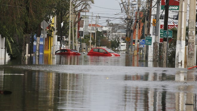 Cars remain on a flooded street in San Juan, Puerto Rico, on Sept. 22, 2017.