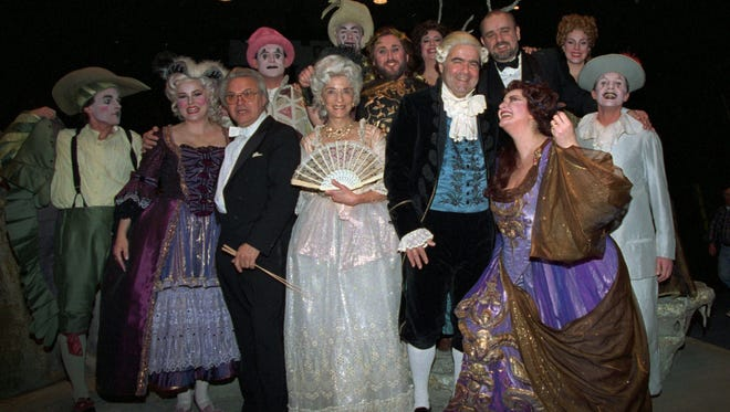 "Supreme Court Justices Ruth Bader Ginsburg, with fan, and Antonin Scalia pose with members of the cast of ""Ariadne auf Naxos"" following a performance of the Washington Opera in 1994."