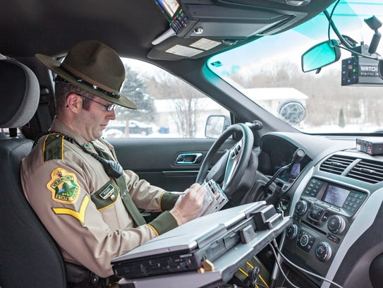 Vermont State Trooper Jay Riggen writes a ticket for