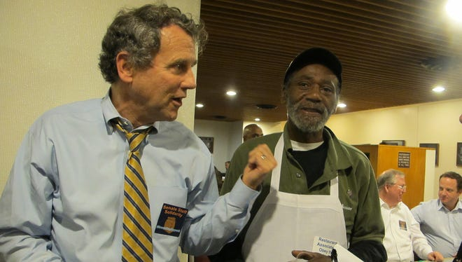 """Sen. Sherrod Brown talks with Charles Gladden, a Senate food service worker, and others, as part of a  """"sit-in"""" to support a wage increase."""
