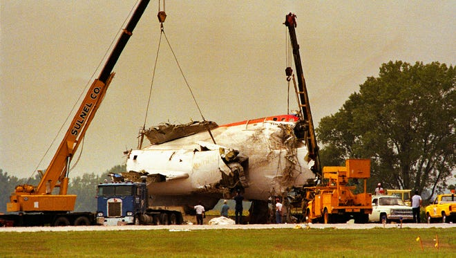 FILE - In this July 22, 1989 file photo cranes lift the tail section of United Airlines Flight 232 onto a truck after the McDonnell Douglas DC-10 carrying nearly 300 people crash landed at the Sioux City, Iowa, airport. It has been 25 years since the crash but its legacy lives on. It changed the way planes were designed, ensuring more backup systems. It drew attention to the need for disaster emergency preparedness. And the heroic work of the pilot and crew has been lauded in movies and books. (AP Photo/James Finley, File)